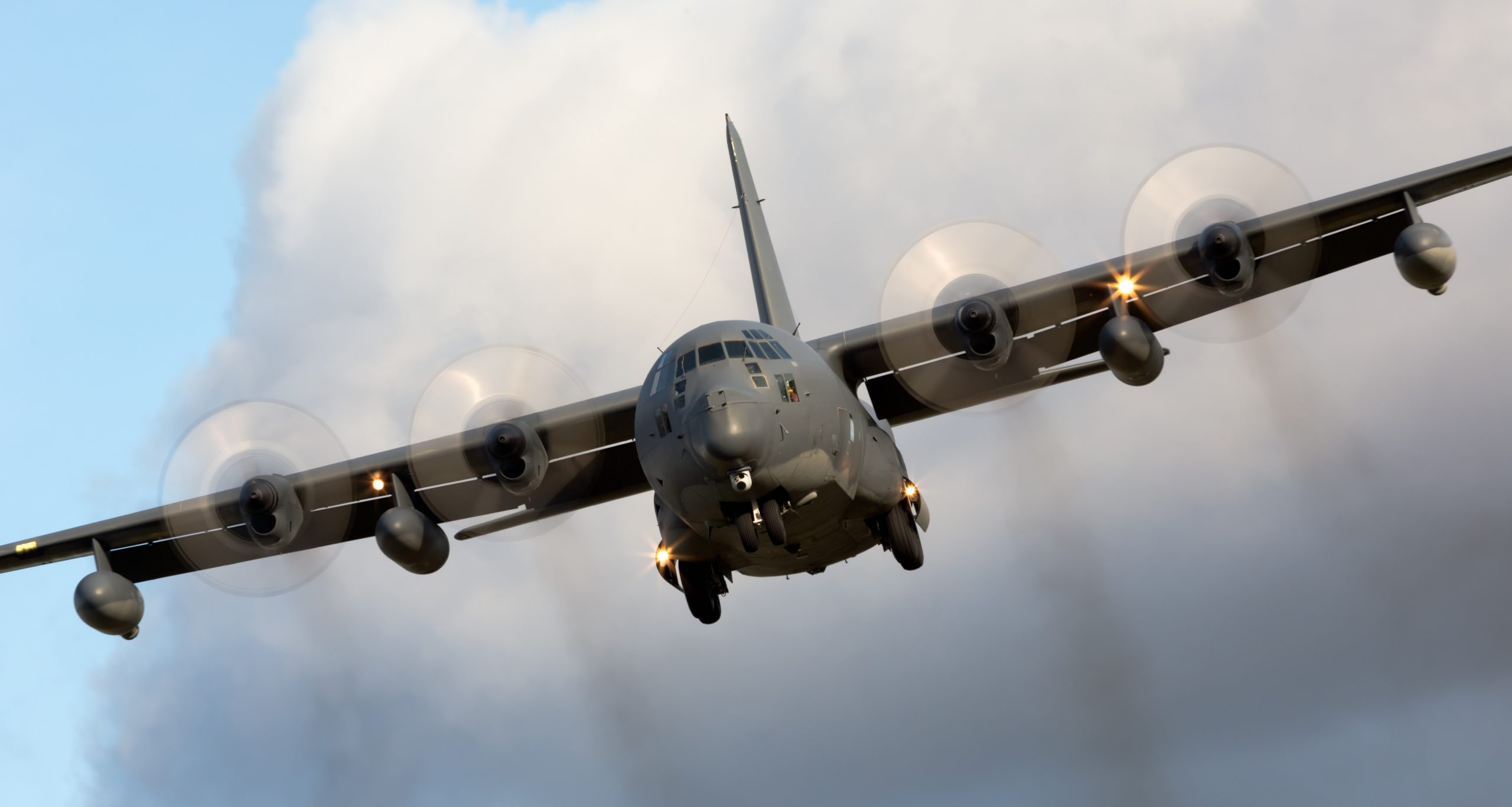 Lockheed MC-130H Hercules with large cloud behind it